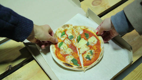 Hungry friends taking pieces of small pizza. Friendship. Fairness. Tasty food Footage
