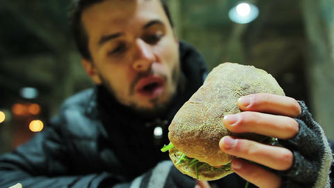 Hungry poor homeless man eating sandwich with vegetables at charity event Live Action