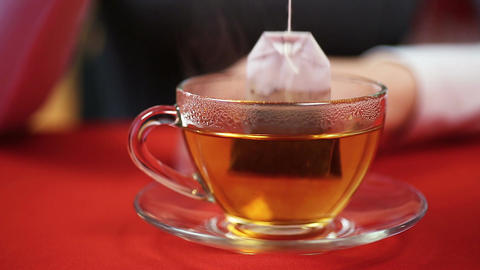 Teatime, female making black tea, putting teabag in a cup. Person feeling cold Footage