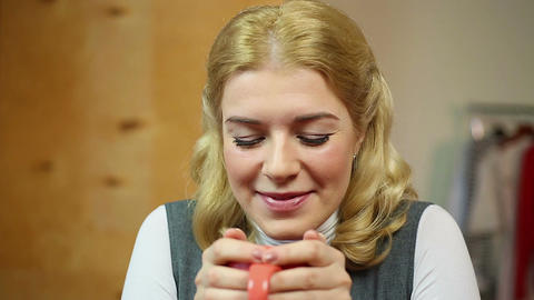 Happy and cheerful girl drinking warm tea with pleasure after feeling cold Footage