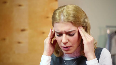 Blond woman having headache, nervous breakdown at work. Stress and problems Live Action