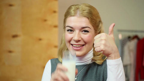 Funny blond woman advertising good quality tasty milk and smiling at camera Footage