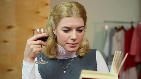 Relaxed woman reading book and drinking a glass of red wine, enjoying leisure Footage