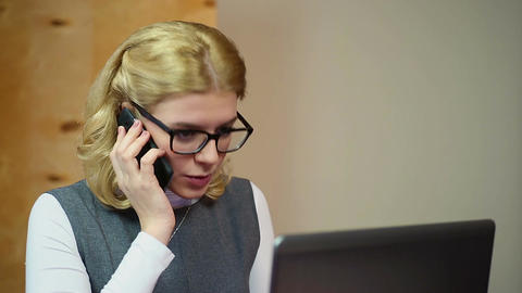 Successful businesswoman working on laptop in office, talking on the phone Footage