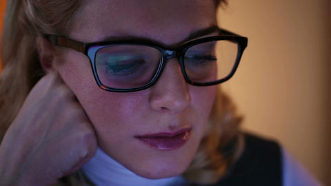 Tired woman wearing glasses, browsing internet pages on laptop at night Footage