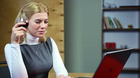 Surprised woman reading latest news on the internet, drinking red wine Footage
