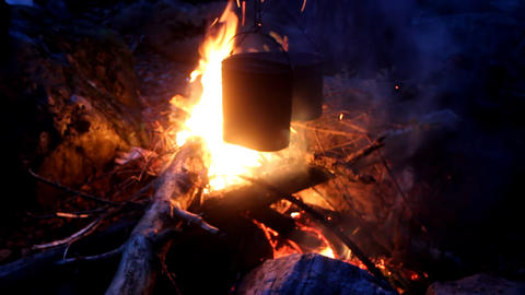 Night bonfire. Dinner is cooked in pots over open fire Footage