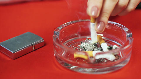 Ashtray with cigarette butts on the table, smoking person. Unhealthy lifestyle Live Action