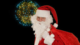 Santa Claus carrying his bag, looks at the camera and winks, fireworks display Animation