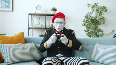 Emotional guy mime playing video game at home losing throwing joystick and Live Action