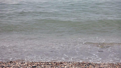 Sea waves with rain drops on the rocky beach Stock Video Footage