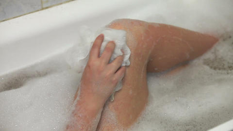 Woman in bath washing her leg with white sponge Stock Video Footage