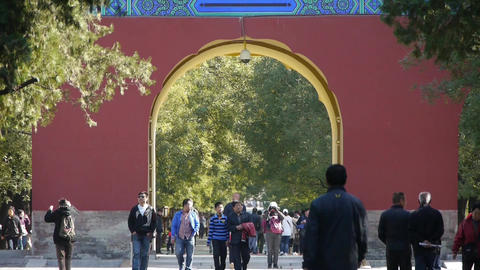 Asian People walk in cypress trees park,China Beijing red door ancient buildings Footage