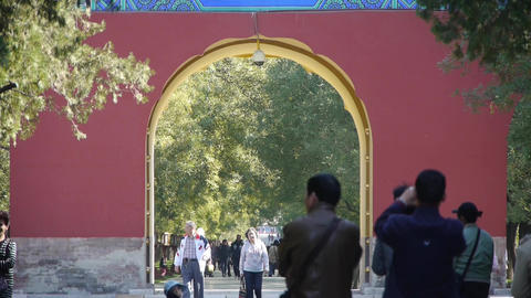 People walk in cypress trees park,China Beijing red door ancient buildings Footage
