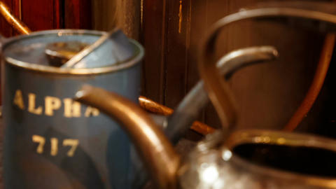 Pull focus shot of two vintage oil buckets next to a working steam engine ビデオ