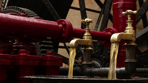 Closeup shot of two industrial faucets pouring oil on an hydraulic engine Footage