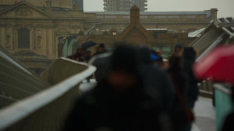 Wide angle shot featuring an anonymous crowd crossing a bridge in London, Englan Footage