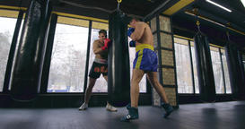 Two boxers training punching bag 4k video in fight club. Fighter holds bag Footage