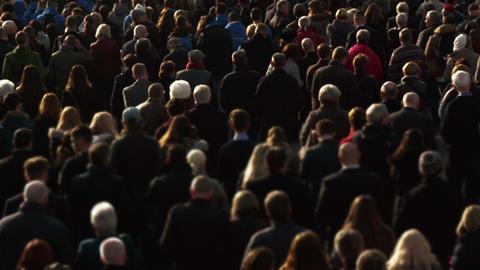 Medium telephoto shot of an anonymous cross-generation crowd attending a memoria Footage