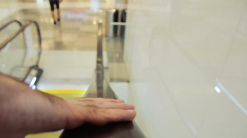 Closeup on anonymous man hand holding an escalator going down in shopping mall Footage
