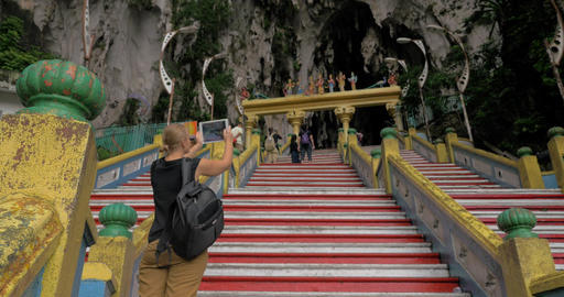 Woman with pad making photo of Batu Caves entrance, Malaysia Footage