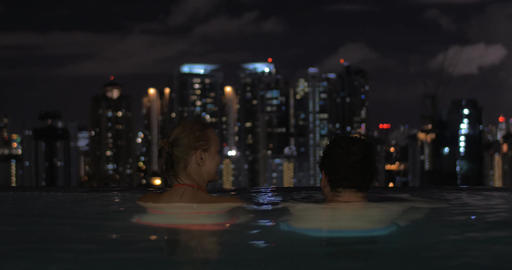 In pool on roof of a hotel in Kuala Lumpur, Malaysia couple in love looking to n Footage