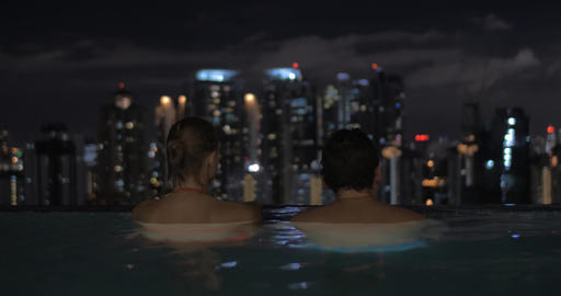 View of woman in the pool on the skyscraper roof and then swimming man about her Footage
