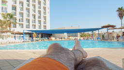 Man relaxing and sunbathing on sunbed by pool Footage