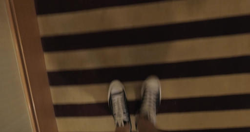 View of looking down at man legs in canvas shoes going on a striped carpet in th Footage