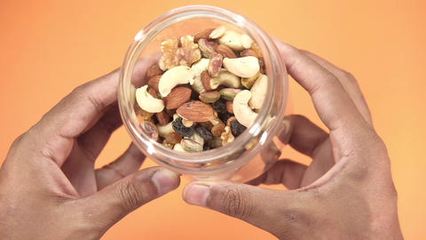 man hand holding a jar of mixed nut Live Action