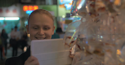 Young blond woman take a picture of gold aquarium fishes packed in plastic bag.  Live Action