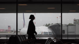 Passenger silhouette pass by against parked airliner, airport scene Footage