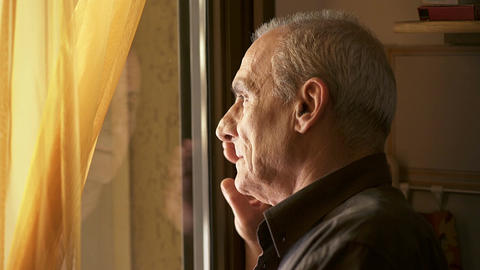 Sad and depressed old man looks out the window Footage