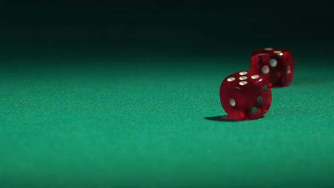 Red dice falling on the green casino table in slow-motion. Gambling game Footage