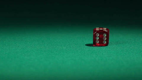 Closeup view of red casino dice rolling on green surface in slow-motion Footage