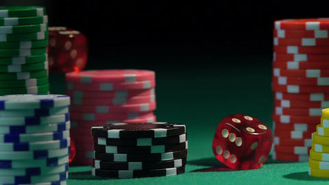 Stacks of chips on green poker table, throwing dice in slow motion. Gambling Footage