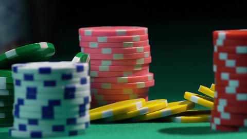 Red dice falling upon colorful chip stacks on green table. Casino gambling Footage