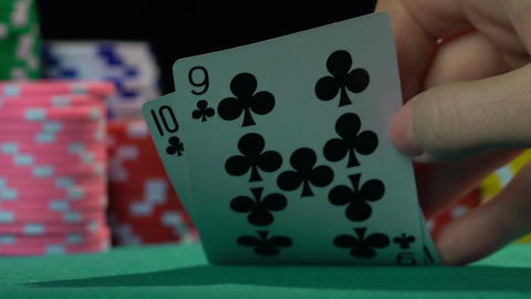 Poker player checking his cards on green casino table, slowmotion. Gambling Footage