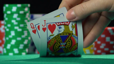 Poker player showing cards, queen and jack of hearts. Unequal love, misalliance Footage