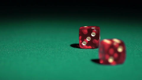 Dice decide destiny, red cubes falling on casino table in slow motion. Gambling Live Action