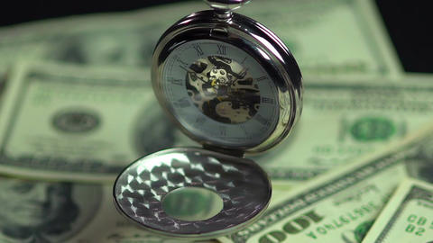 Closeup of vintage pocket watch hanging above money, precious time passing by Footage