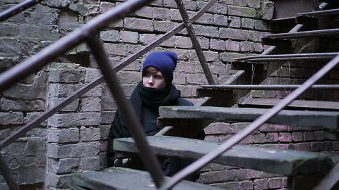 Scared male teenager hiding behind old brick building, looking out cautiously Footage