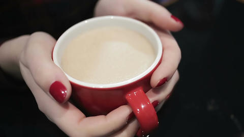 Closeup shot of female hands holding cup of hot latte, woman enjoying coffee Footage