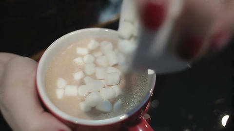 Close-up shot of female hands adding sweet marshmallow to cup of hot coffee Footage