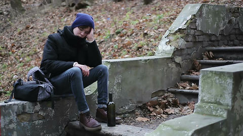 Upset teenager drinking alcohol from bottle in park, suffering from depression Footage