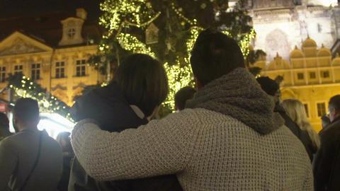 Loving couple admiring beautiful view of decorated luminous Christmas Tree Footage