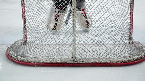 Feet of ice hockey goaltender taking up position in goal crease, protecting net Footage