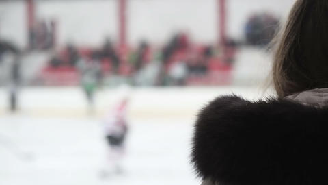 Excited female supporter watching hockey match, team players skating on ice rink Live Action