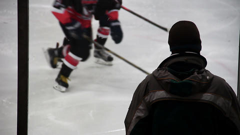 Strict coach watching hockey team players practicing on ice rink, view from back Live Action
