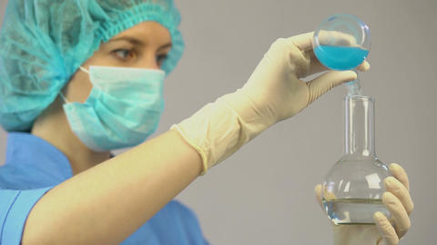 Researcher making experiment in laboratory mixing two liquid, medicine, vaccine Footage